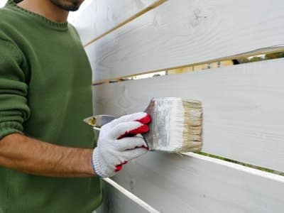 Man painting fence