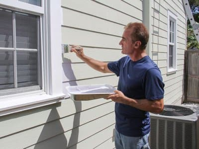 Man painting house siding
