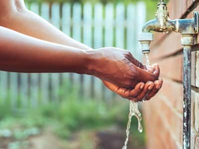 Man uses outdoor faucet to rinse hands