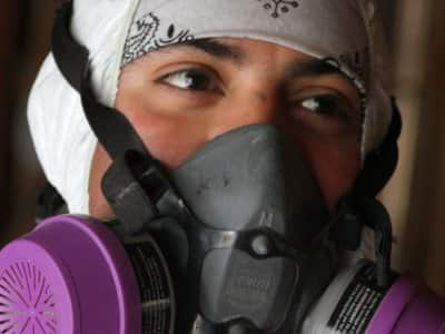 a mold removal specialist in a breathing mask.