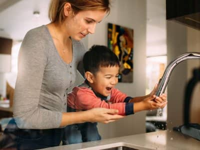 A mother helping her son to wash his hands
