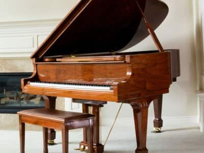 Grand piano in living room with fireplace