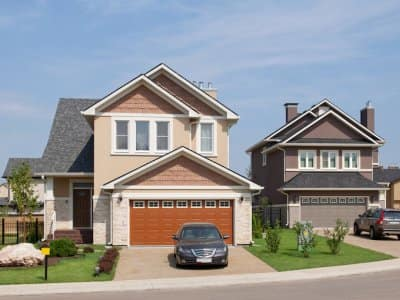 Brand new two-story suburban house in sunny summer afternoon with orange garage door