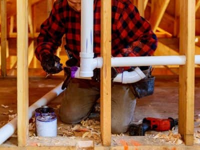 plumber installs pipes in a home