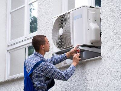 Professional repairing window air conditioner from outside
