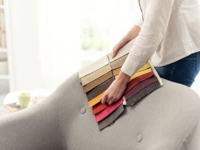 Professional decorator choosing the best upholstery for the armchair by holding fabric samples against it