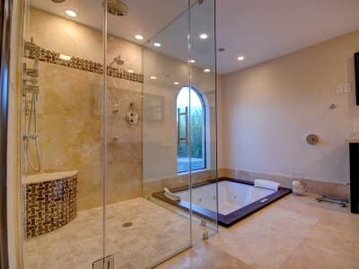 remodeled bathroom with jacuzzi tub, multiple shower heads tile
