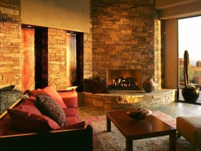 fireplace in living room opening up to a desert scene