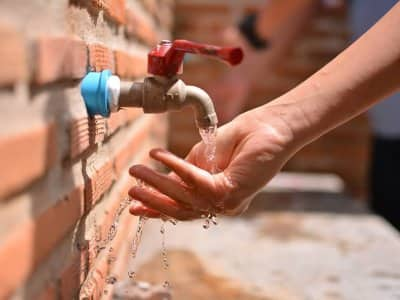 Person washing hands under a spigot in a brick wall