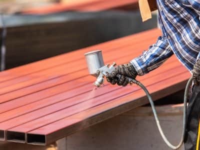 Worker spraying paint to steel pipe