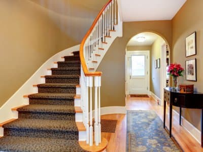 stairs and railing lead upstairs while hallway features arched doorway and entry way table