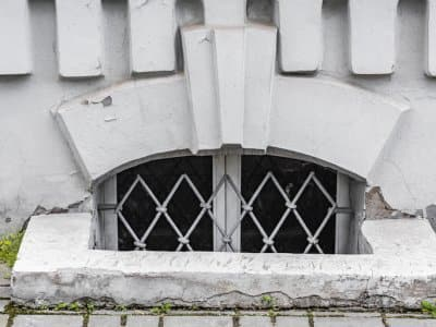 basement window with wire bars sits behind stone square egress with decorative stone details above window