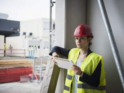 a strucutral engineer on a job site. she holds a tablet