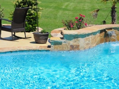 closeup of swimming pool with stone edge, concrete patio, and black lawn chair