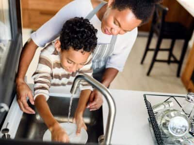 Mother and son washing dishes together