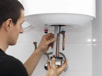 person repairs pipes of water heater