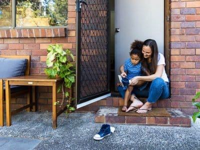 Woman helping child put on shoes with an open screen door