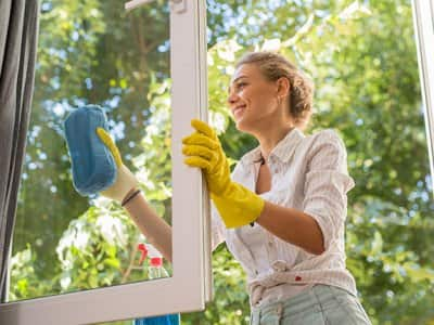 A woman wearing gloves cleaning her windows