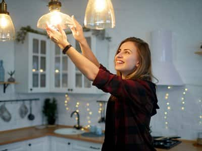 Woman screws in bulb on hanging light