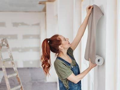 Young woman tries out a new wallpaper