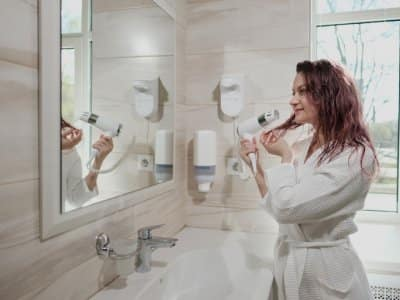 woman in white robe in white bathroom uses hairdryer and smiles