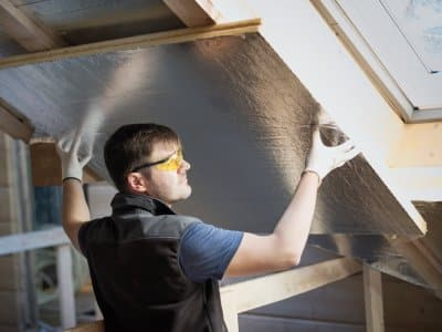A professional placing insulation in attic