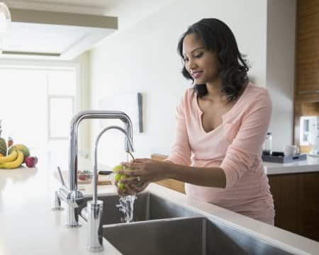 Woman washes grapes in kitchen sink