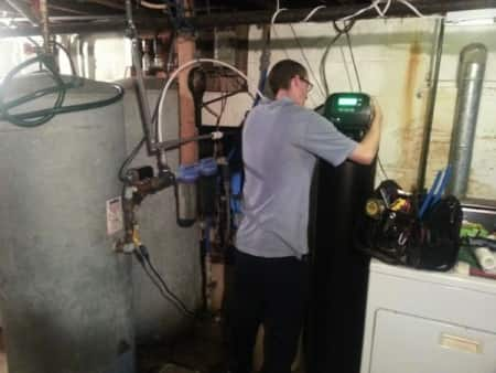 Service technician Jason Amerson installs a water softener in a Columbus-area home. (Photo courtesy of Robert Miller)