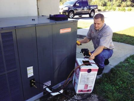 technician performs an outside service check on an air conditioning unit.