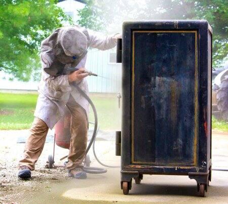 Craftsman using coal slag gun to strip dirt of an antique safe