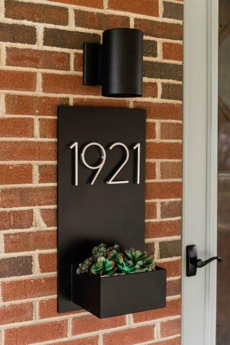 a black planter box displaying the house number and containing a succulent is attached to a brick wall (Photo by © Carrie Waller)
