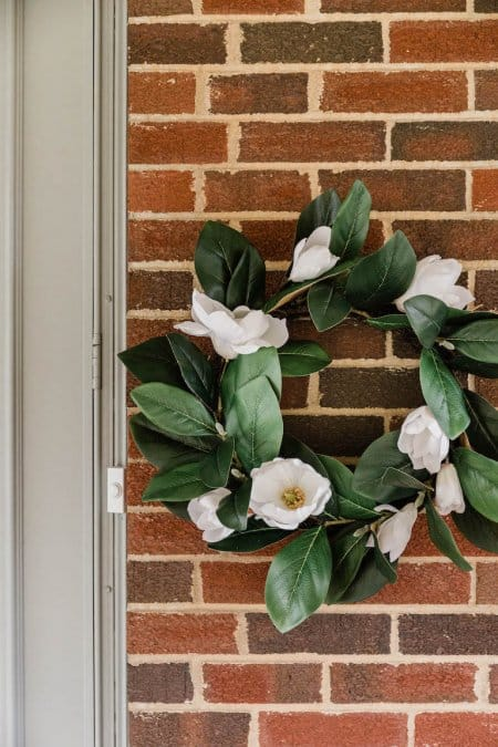 wreath of green leaves and white flowers against red brick wall (Photo by © Carrie Waller)