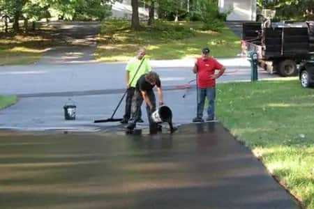 contractor pouring sealant on asphalt driveway