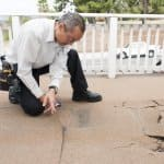 man inspecting a damaged deck