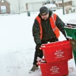 A Ray's Trash Service worker stops by the curb to pick up recycling. (Photo by Brandon Smith)