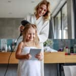 Mom using a hair dryer to dry daughter's hair (Photo by Yakobchuk Olena - stock.adobe.com)