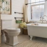A bathroom with a white bathtub and tiled floor (Photo by Perry Mastrovito/Image Source via Getty Images)