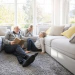 elderly man and two young kids read book in front of large windows between two white couches (Photo by  Westend61 via Getty Images)