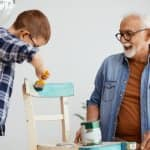 Grandfather and grandson painting a chair blue (Photo by Drazen Zigic / Shutterstock.com)