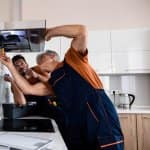 Handyman working under vent with homeowner (Photo by BAZA Production/Shutterstock.com)