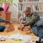 Dad and son build blocks on hardwood floors (Photo by katleho Seisa / E+ via Getty Images)
