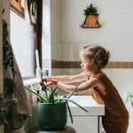 little girl washing hands in bathroom with plants  (Photo by Catherine Falls Commercial/Moment via Getty Images)