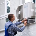 Professional repairing window air conditioner from outside (Photo by Andrey Popov - stock.adobe.com)