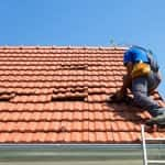 Roof repairman fixing a tile roof (Photo by © sharplaninac - stock.adobe.com)
