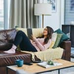 Woman on couch with blanket and electronic device (Photo by Charday Penn/E+ via Getty Images)