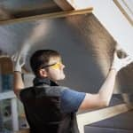 A professional placing insulation in attic (Photo by Mikael Vaisanen/The Image Bank via GettyImages)