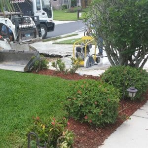 Workers removing a concrete driveway