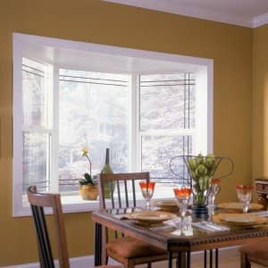 White bay window and brown kitchen table.