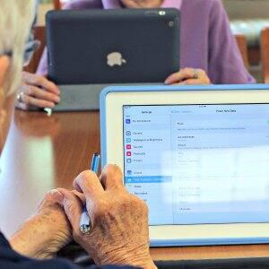 Elderly man using iPad internet screen with aged hands