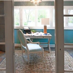 remodeled sun room with desk and chair in front of windows